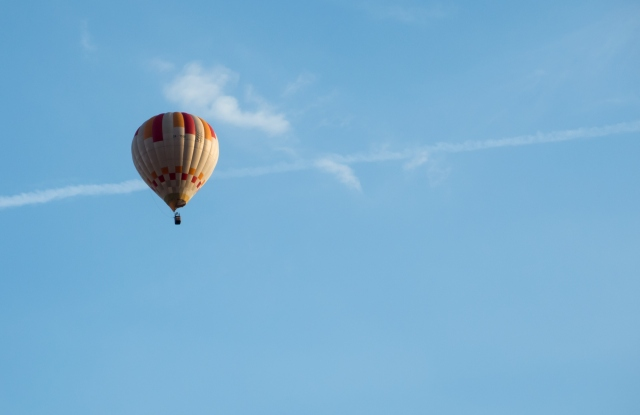 A photo of a hot-air balloon high up in a blue sky, taken from the ground