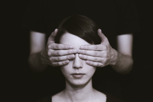 A sepia-tinted photo of a woman's head with the hands of a person behind her, out of focus, covering her eyes