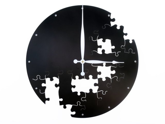 A photo of black clock on a white background with puzzle piece-shaped cutouts randomly placed over the lower three quarters of the clock