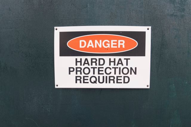 """A photo of a warning sign that reads """"DANGER, HARD HAT PROTECTION REQUIRED"""""""