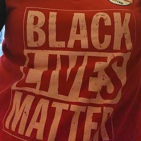 "Photo of a person wearing a red t-shirt with the slogan ""Black Lives Matter."" The slogan fills the entire frame."