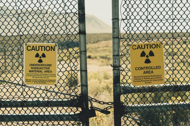 Photograph of chain-locked wire fencing with radiation warning signs