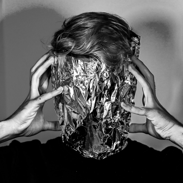 Black and white photo of man holding a large piece of tinfoil over his face.